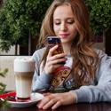 A teenaged girl looks at her cell phone while she drinks a milkshake.