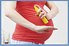 pregnant woman spraying mosquito repellant